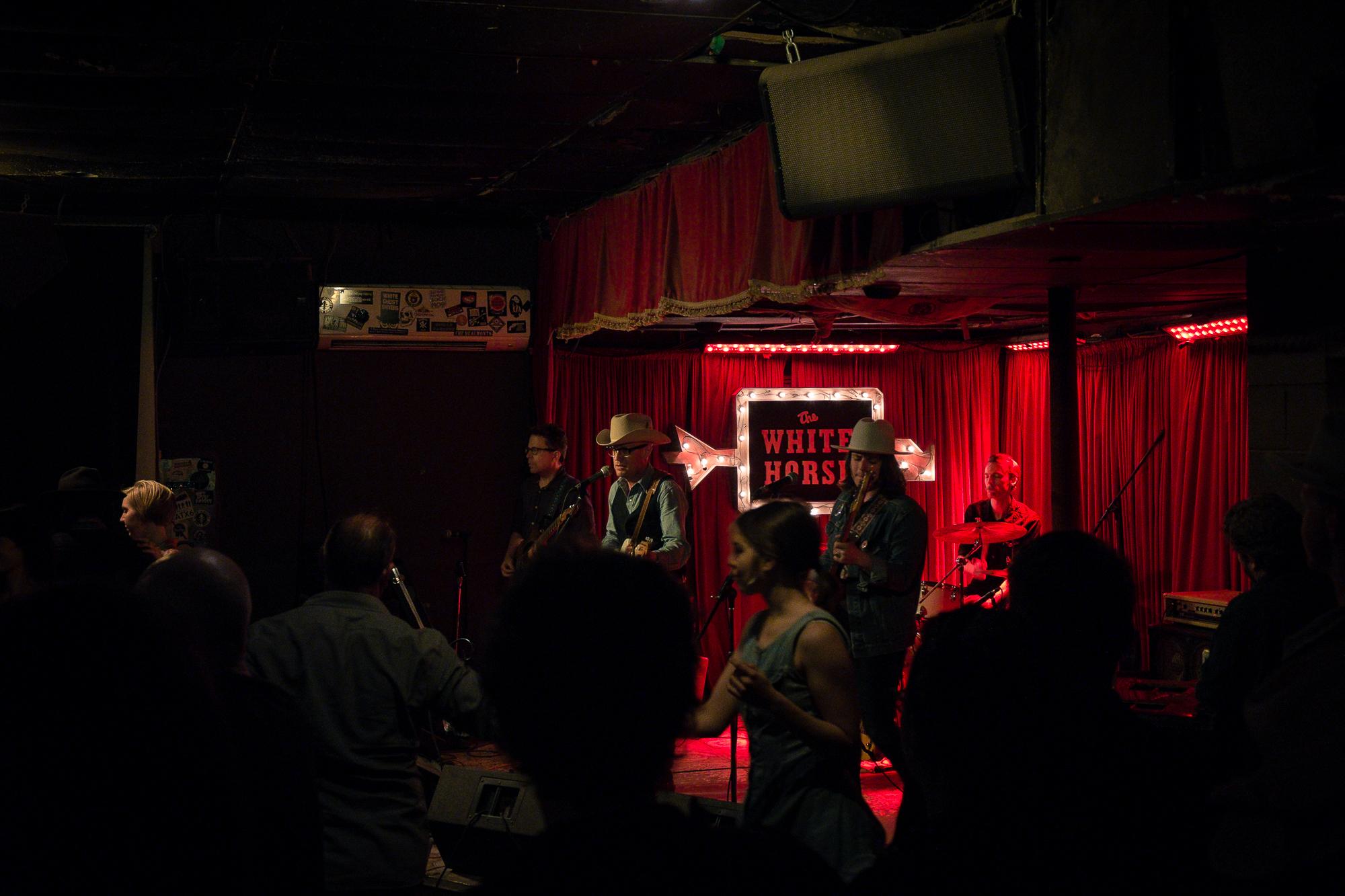 Pessoas dançando ao som de uma banda de música country.